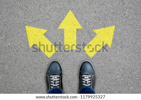 Black shoes standing at the crossroad making decision which way to go - three ways to choose. #1179925327