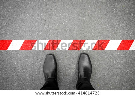 black shoes standing at the red-white line. Do not cross the line. It's prohibited and not allowed. It's limited. It's the end. Foto d'archivio ©