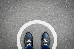 Black shoes standing in white circle on the asphalt concrete floor. Concept of limit, boundary, frame, etc.