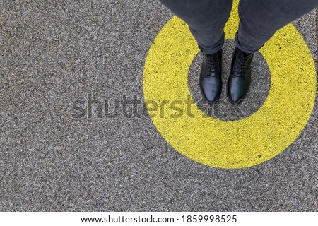 Black shoes standing in yellow circle on the asphalt concrete floor. Comfort zone or frame concept. Feet standing inside comfort zone circle. Place for text, banner Imagine de stoc ©