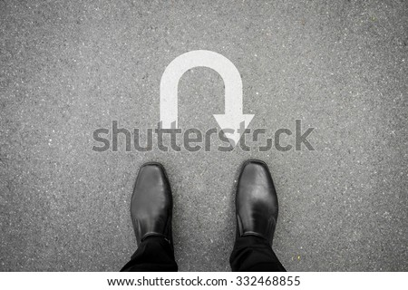 black shoes standing on the asphalt concrete floor in front of u turn symbol #332468855