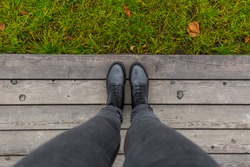 Black shoes standing on the wooden pier. Feet shoes walking in outdoor. Youth Selphie Modern hipster