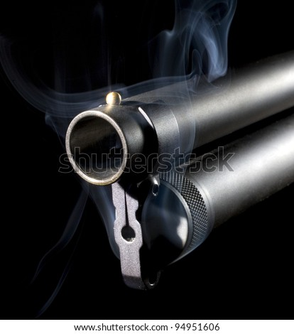 Black shotgun that has smoke coming from around its barrel