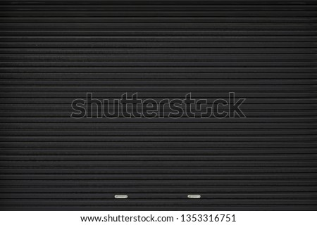 black shutter door with stainless steel holder. grunge black metal foldable door background and texture. Stock photo ©