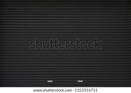 black shutter door with stainless steel holder. grunge black metal foldable door background and texture.