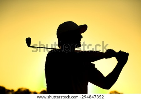 Black silhouette close-up of male golf player with hat teeing-off at beautiful golf course. Professional golf player smiling.