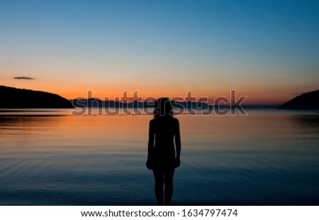 black silhouette of a woman on the background of a stunning orange and blue sunset on the sea, the sunset sky is reflected in the water