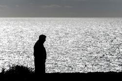 Black silhouette of an old man in typical hat strolling on the edge of a cliff, with the sea glowing in the background