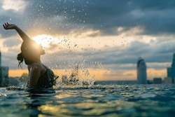 Black silhouette of asian woman splash water on summer vacation holiday relaxing in infinity swimming pool with blue sea sunset view with high rise skyscape urban downtown Healthy happiness lifestyle
