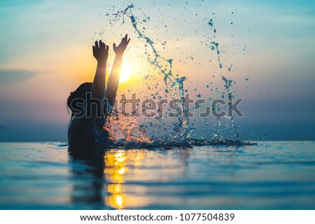 Black silhouette of asian woman splash water on summer vacation holiday relaxing in infinity swimming pool with blue sea sunset view. Healthy happiness lifestyle