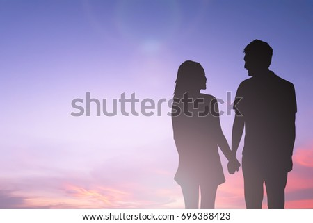 black silhouette of couples lover holding hand and looking each other on blurred beautiful sunset sky in honeymoon moment,just married concept