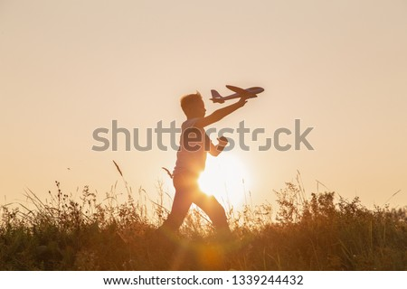 Black silhouette of cute happy cheerful child running fastly along grassy hill at countryside holding big toy plane in hand. Boy playing during sunset time in evening. Horizontal color photography.