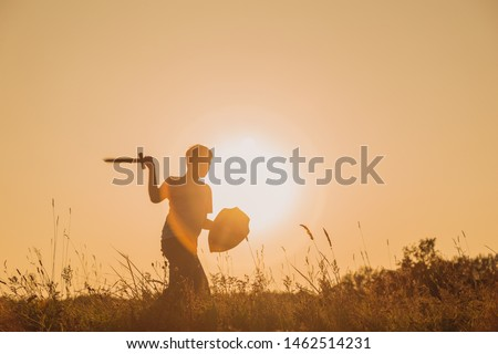 Black silhouette of cute young caucasian kid isolated on sunny orange sunset or sunrise sky background playing sword with invisible enemy. Horizontal color photography.