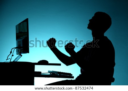 Black silhouette of happy teenager sitting at the computer on blue background