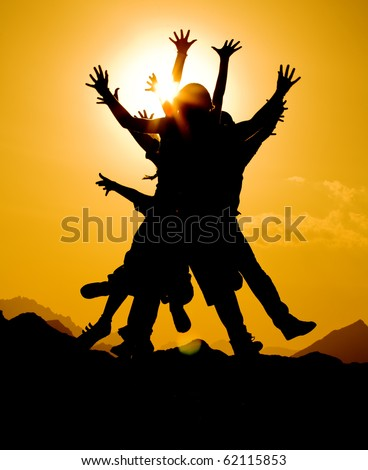 black silhouette of people group in happy jump on orange sunset sky and desert mountain background