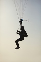 Black silhouette of skydiver pulling brakes before landing, close-up.
