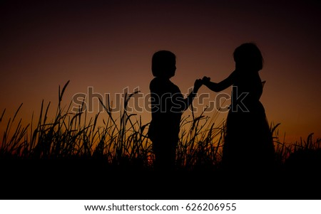 Black silhouette of Two Asian little girl standing on a grass field background of gorgeous sunsets. The girl giving promise and show hand sign language.