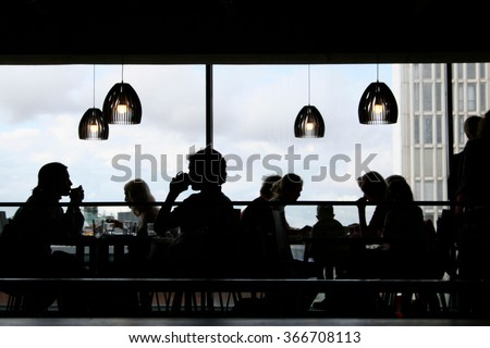 Black silhouettes of people having lunch inside a modern restaurant with big windows #366708113