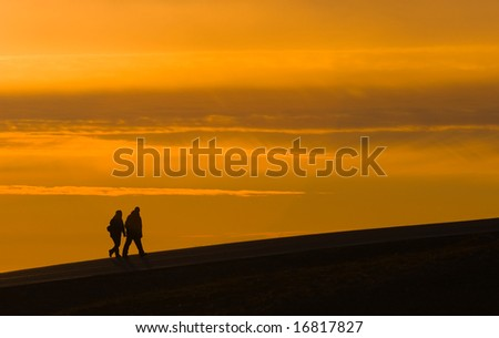 black silhouettes of two walking tourists on sunset sky background