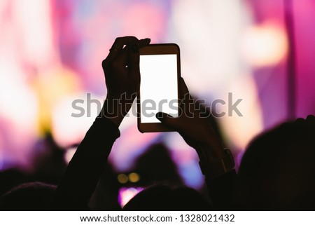 Black silhoutte of music fan with smartphone on dance floor filming video and taking pictures on popular edm musical festival in nightclub.Empty white mobile phone screen to place event logo #1328021432