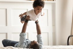 Black single father lying on bed, holding in arms, lifting funny little african american curly cute son in bedroom. Overjoyed child boy feels like plane, having fun, playing with smiling dad on bed.
