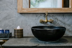 Black sink, vintage copper faucet, gray wall, mirror, loft bathroom interior details. Close up, minimalism concept