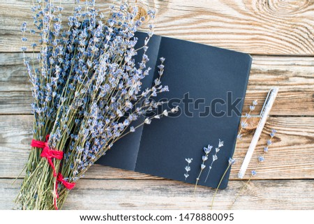Black sketchbook with space for your text and bouquet dried lavender flowers on an old wooden background