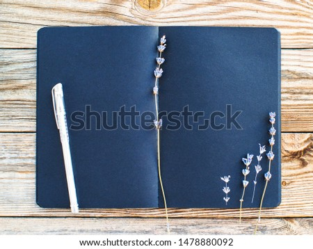 Black sketchbook with space for your text and dried lavender flowers on an old wooden background