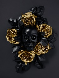 Black skull surrounded with golden rose flowers and black leaves isolated on a black background. Creative Halloween or Santa Muerte concept. Minimal dark romantic idea. Flat lay.