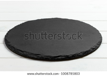 Black slate round stone on wooden background, top view, copy space. ストックフォト ©