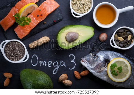 Black slate table with product rich in omega 3 and vitamin D. Written word omega 3 by white chalk. #725527399