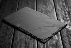 Black slateboard on dark wood