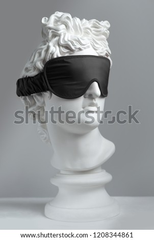 Black sleeping mask.  Gypsum statue of Apollo's head. Man. Statue. Plaster statue of Apollo's in black sleep mask.