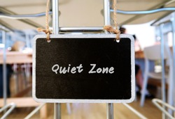 Black small chalkboard hanging in coworking space with text handwritten Quiet Zone, concept of an area in coworking space or library or office which need silence , or an introvert need privacy