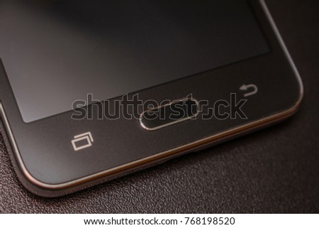 Black smartphone from below on a black matte background