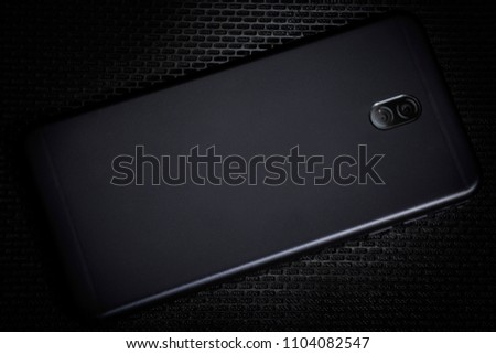 Black smartphone on background metal