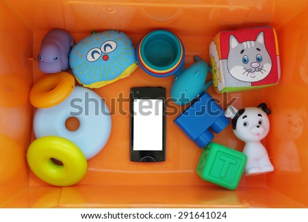 Black smartphone with white screen in a box with toys