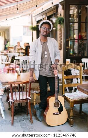 black smiling man wearing formals playing a guitar #1125469748