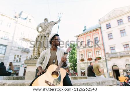 black smiling man wearing formals playing a guitar #1126262543