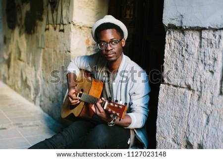 black smiling man wearing formals playing a guitar #1127023148