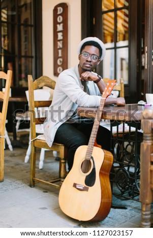 black smiling man wearing formals playing a guitar #1127023157