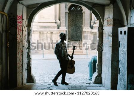 black smiling man wearing formals playing a guitar #1127023163
