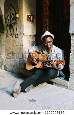 black smiling man wearing formals playing a guitar #1127023169