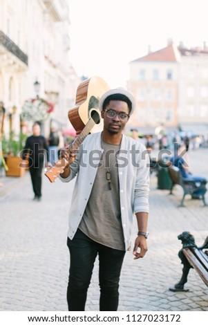 black smiling man wearing formals playing a guitar #1127023172