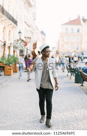 black smiling man wearing formals walking with guitar #1125469691