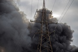 Black smoke from a fire over the city against a cloudy sky with a high-voltage tower