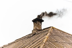 Black smoke from the chimney of an apartment building during heating and heating on the roof of slate.