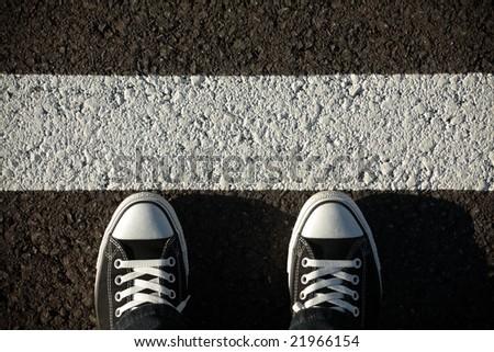 Black sneakers on asphalt, top view
