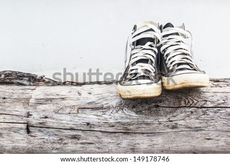 black sneakers on the old Log wood  and gray concrete walls