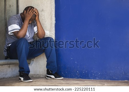 Black South African man sitting in a corner to depict depression and stress that men are suffering from in Africa.